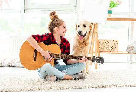 Girl playing guitar with lovely dog 免版税图像