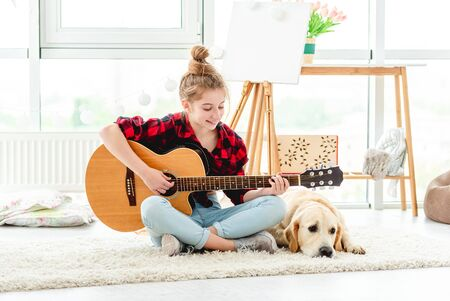 Young girl with guitar near dog 免版税图像