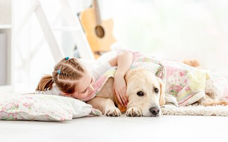 Beautiful little girl covering cute dog with blanket on floor in playroom