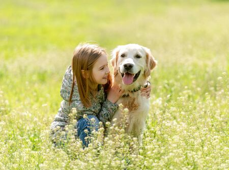 Smiling little girl looking at cute dog