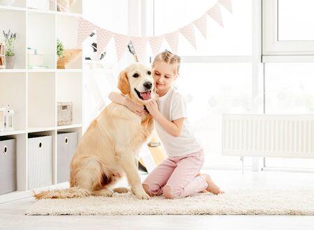 Happy little girl cuddling beautiful dog