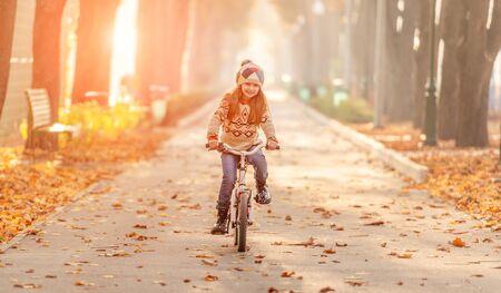 Happy girl riding bike in park