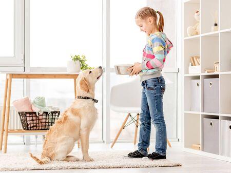 Beautiful girl feeding cute dog