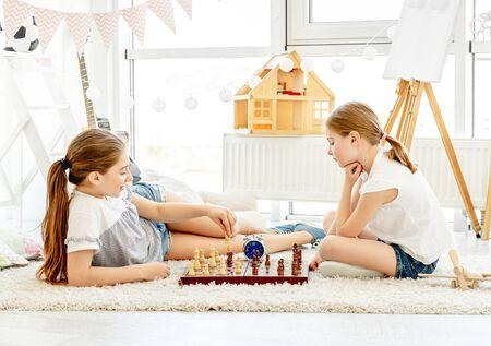Pretty girls playing chess game