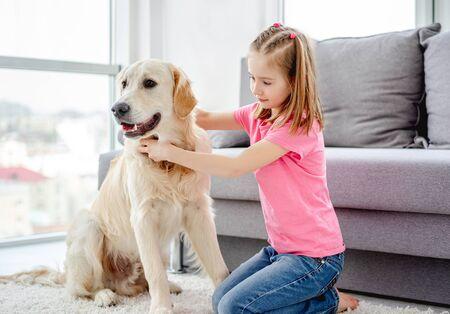 Pretty little girl with golden retriever