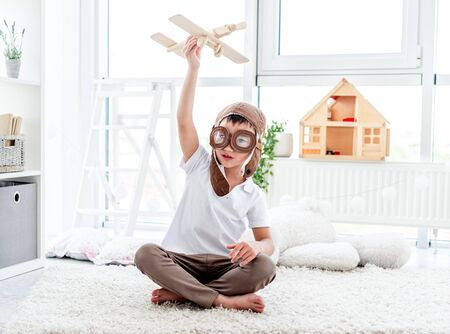 Happy little boy in pilot hat playing with wooden plane in children's room