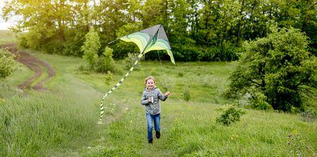 Happy little girl flying bright kite outdoors on nature in spring 免版税图像
