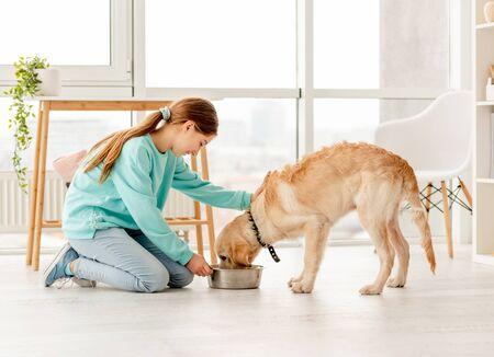 Cheerful owner feeding cute dog