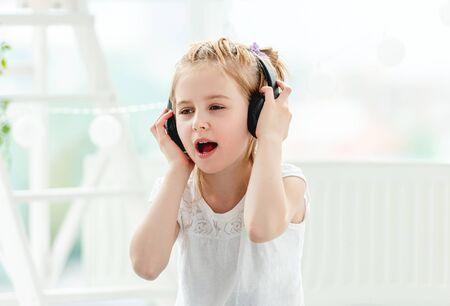 Beautiful little girl wearing headphones