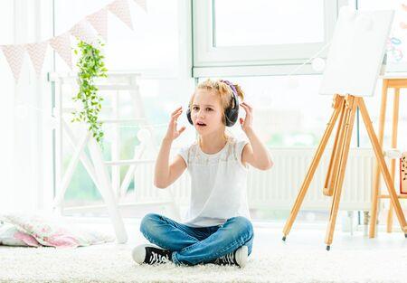 Cute little girl in headphones singing 免版税图像