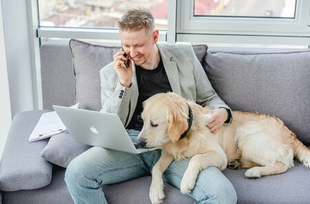 Handsome man cuddling dog while working