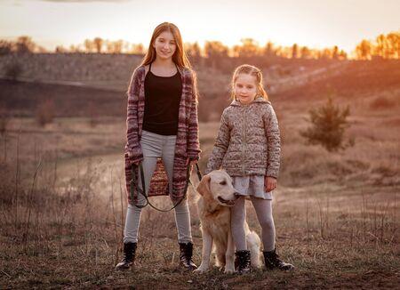 Cute sisters hugging dog outdoors 免版税图像