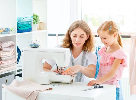 Little girl is taught to sew