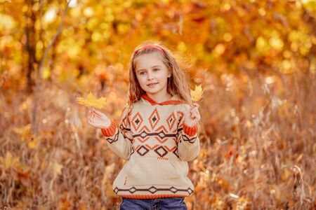 Cute girl holding yellow leaves