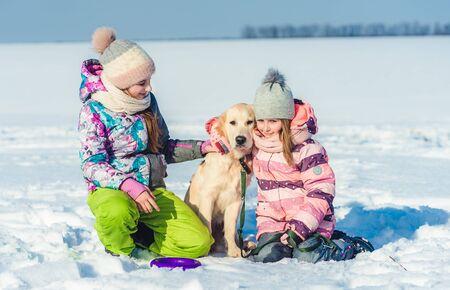 Sisters hugging dog on winter day 免版税图像