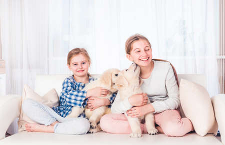 Smiling sisters sitting with puppies 스톡 콘텐츠