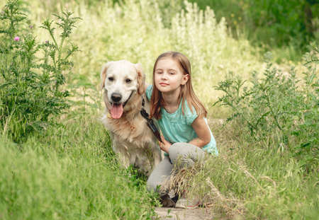 Little girl with golden retriever on meadow