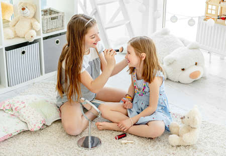 Smiling kids applying make up cosmetics Foto de archivo - 152258849