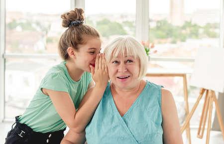 Little girl whispering secret to grandmother