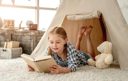 Nice little girl with paper book Foto de archivo