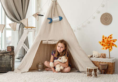 Little girl hugging plush teddy in wigwam Foto de archivo - 152258998