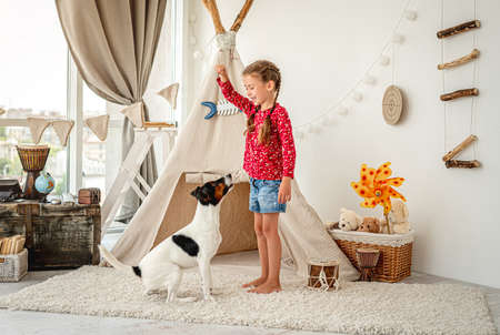 Girl child training fox terrier dog