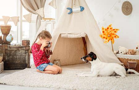 Little girl photographing fox terrier indoors Stock fotó