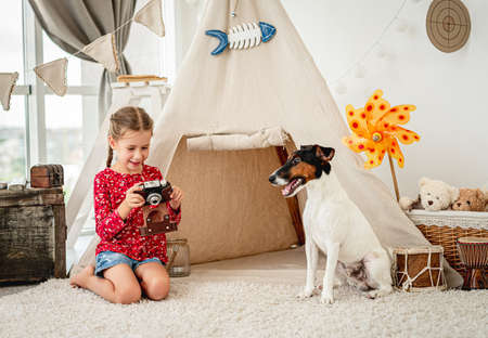 Little girl with camera next to dog