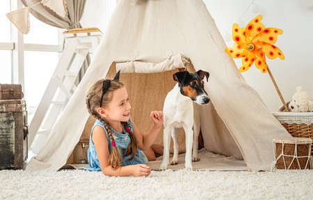 Little girl in wigwam with fox terrier Stock fotó