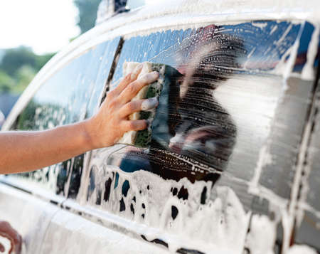 Hand with sponge washing car window Foto de archivo
