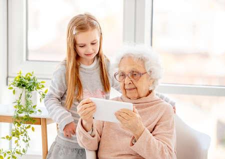 Cute girl helping old lady Foto de archivo