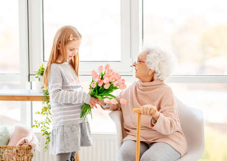 Girl presenting bouquet to old woman Foto de archivo - 152259086