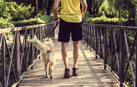 Man jogging across bridge with dog 스톡 콘텐츠 - 152517148