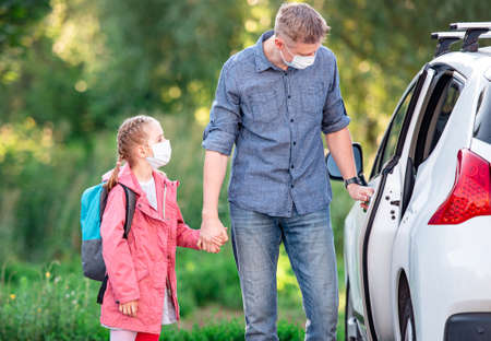 Father driving daughter to school during pandemic