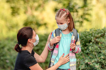 Mother putting mask on daughter before school