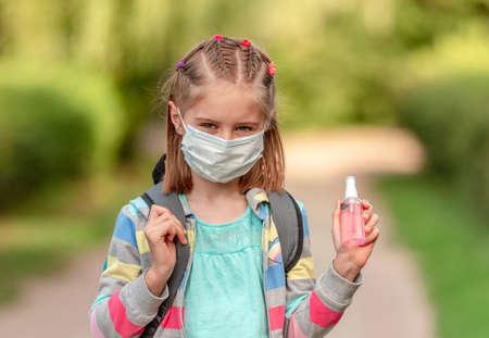 School girl in mask holding sanitizer
