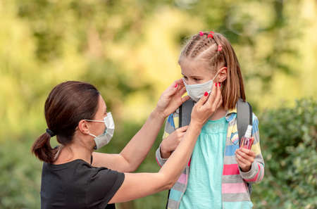 Mother putting mask on daughter before school 스톡 콘텐츠