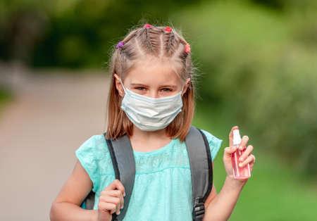 School girl in mask holding sanitizer 스톡 콘텐츠 - 152955817
