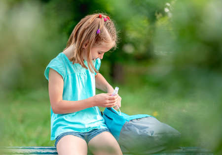 School girl with sanitizer on bench