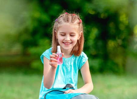 School girl in mask holding sanitizer 스톡 콘텐츠 - 152955822
