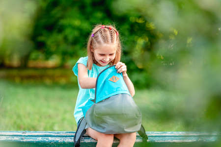 Schoolgirl peeking into backpack in park Foto de archivo