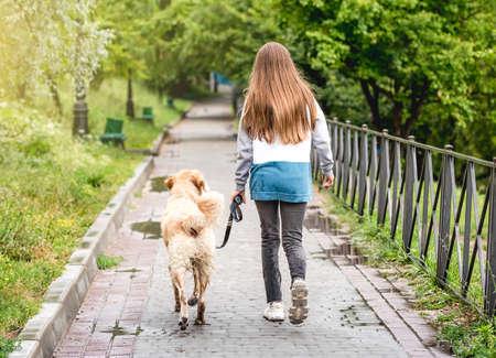Girl walking dog along wet alley