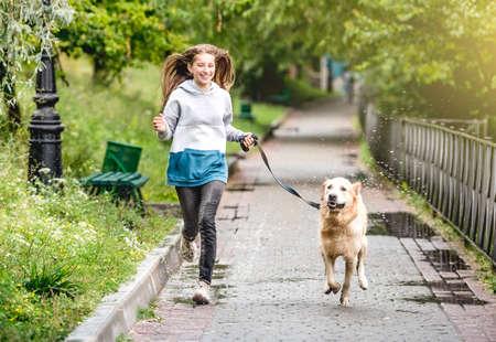 Teenage girl running with dog after rain 스톡 콘텐츠 - 152955828