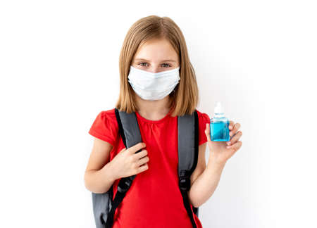 Schoolgirl in medical mask holding sanitizer 스톡 콘텐츠 - 152955830