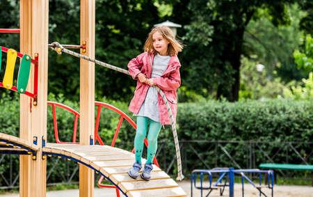 Little girl climbing rope on playground