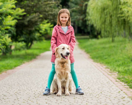 Little girl standing with dog between feet 스톡 콘텐츠 - 153211626