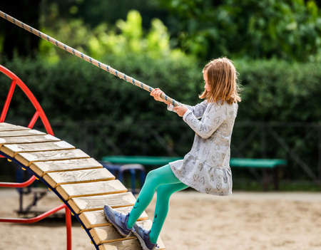 Child climbing with rope on playground 스톡 콘텐츠 - 153049030