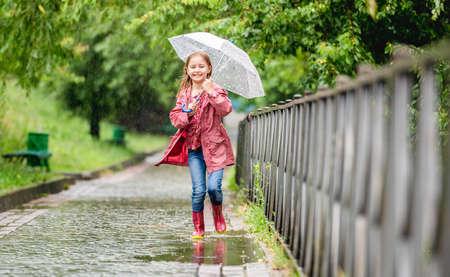 Little girl running through puddles