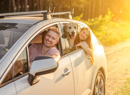 Father driving car with daughter and dog
