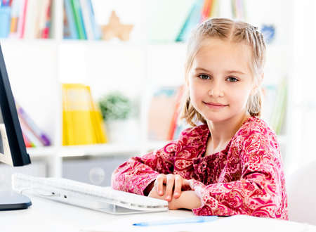 Little girl sitting in front of computer
